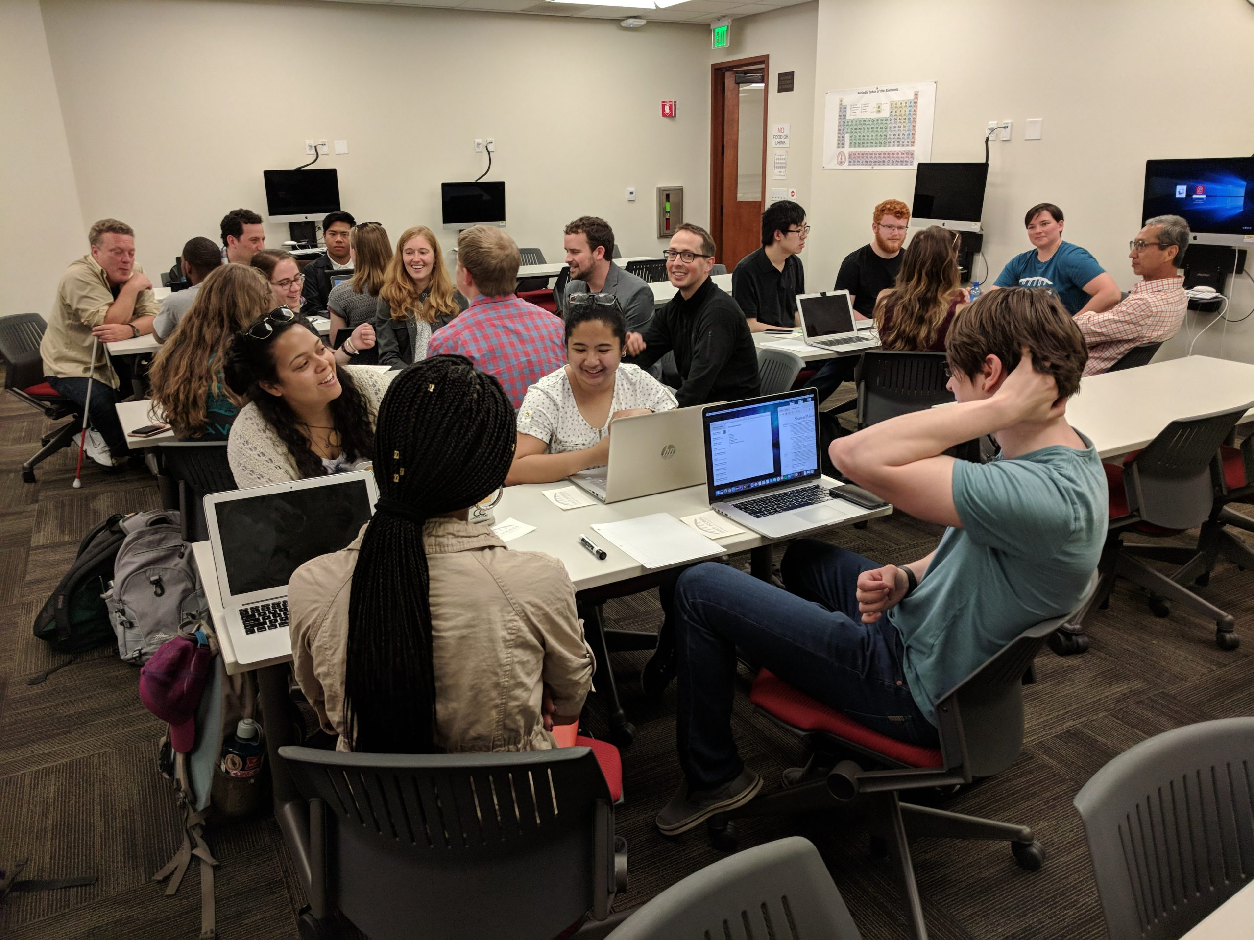 Room of students in conversation, seated in groups of 4-6 at tables