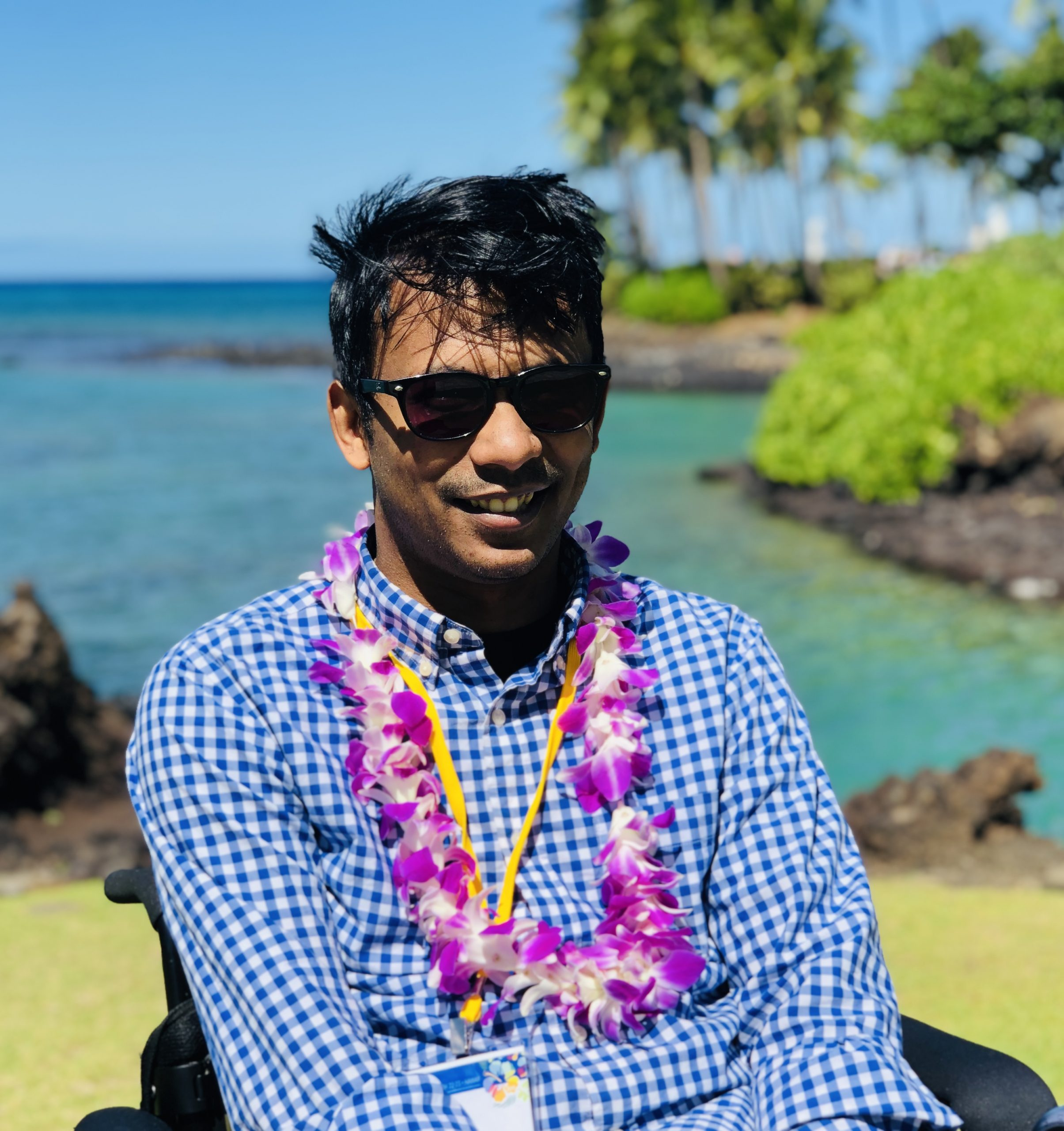 Ather Sharif smiling, wearing flower lei and sunglasses